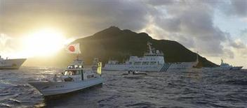 Китайское разведывательное судно (в центре) проплывает мимо острова Уоцури, принадлежащего к спорному архипелагу Сенкаку (япон.) или Дяоюй (кит.) в Восточно-Китайском море, 1 июля 2013 года. Государственные нефтяные компании Китая намерены инвестировать $5 миллиардов в освоение газовых месторождений в Восточно-Китайском море в непосредственной близости от территории, на которую заявляет права Япония. Mandatory Credit. REUTERS/Kyodo