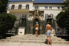 An unidentified couple look through the gates to Casa Casuarina on Ocean Drive in the south beach district of Miami Beach in this July 10, 2007 file photo. REUTERS/Hans Deryk/Files
