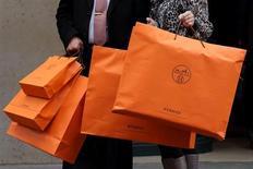 Пара стоит с пакетами у магазина Hermes в Париже 21 марта 2013 года. Французская Hermes нарастила продажи во втором квартале на 16 процентов при постоянном валютном курсе и немного улучшила свой прогноз выручки на весь год. REUTERS/Philippe Wojazer