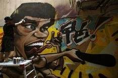 Artista pinta grafite da lenda do Kung Fu Bruce Lee na parte externa de uma galeria em Hong Kong. O astro de kung fu Bruce Lee pode ser um ícone internacional, mas ainda não é um herói totalmente reconhecido em Hong Kong. O astro de kung fu Bruce Lee pode ser um ícone internacional, mas ainda não é um herói totalmente reconhecido em Hong Kong. 16/07/2013. REUTERS/Bobby Yip