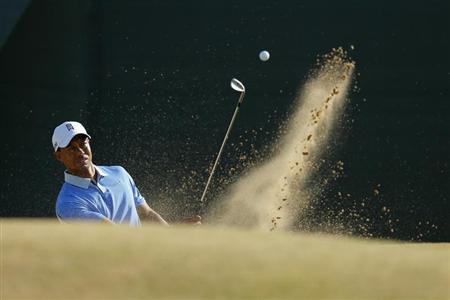 Tiger Woods hits out of a bunker on the 11th hole during a practice round ahead of the British Open golf championship at Muirfield in Scotland July 17, 2013. REUTERS/Brian Snyder
