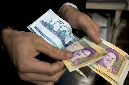 A vendor counts money in a shop in Tehran's Grand Bazaar January 19, 2009. REUTERS/Raheb Homavandi