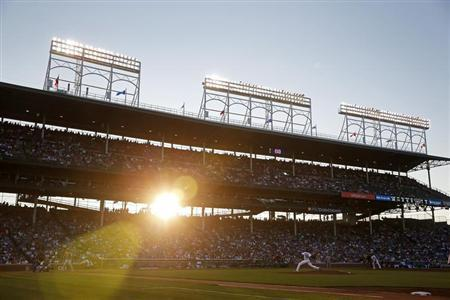Chicago Cubs' Edwin Jackson (R) pitches against St. Louis Cardinals' Pete Kozma as the sun sets during the third inning of their National League MLB baseball game in Chicago, Illinois, July 11, 2013. REUTERS/Jim Young