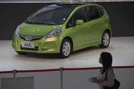 A woman walks past a Honda Fit Hybrid car during the media preview of the 10th China International Automobile Exhibition in Guangzhou November 22, 2012. REUTERS/Tyrone Siu