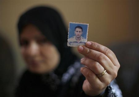 The wife of Palestinian Wael Abu Rida holds his picture at his house in Khan Younis in the southern Gaza Strip June 30, 2013. REUTERS/Ibraheem Abu Mustafa