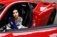 "Halima Miah, 16, arrives in a Ferrari for a parade of ""supercars"" at Swanlea School graduation day in Tower Hamlets, east London July 2, 2013. REUTERS/Olivia Harris"