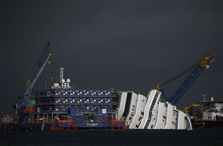 The capsized cruise liner Costa Concordia is surrounded by cranes during a salvage operation in front of Giglio harbour in this January 11, 2013 file photo. REUTERS/Tony Gentile/Files