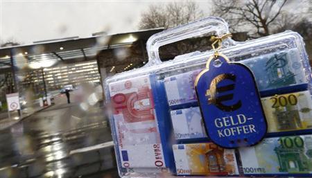 A money suitcase (Geldkoffer) containing chocolate euro notes is pictured outside the headquarters of Germany's federal bank Deutsche Bundesbank in this picture illustration taken in Frankfurt February 4, 2013. REUTERS/Kai Pfaffenbach
