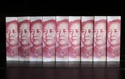 Банкноты валюты юань в Пекине 11 июля 2013 года. Решение Пекина отменить минимальный допустимый уровень кредитной ставки не станет решающим фактором для китайских банков, но с него может начаться обратный отсчет до реформы, которая отнимет у банков их фактически безрисковые прибыли. REUTERS/Jason Lee