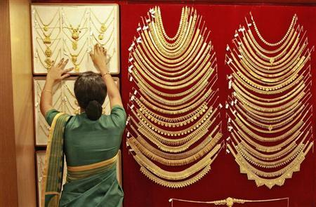 A saleswoman arranges a gold necklace inside a jewellery showroom in Kochi April 16, 2013. REUTERS/Sivaram V/Files