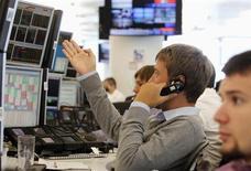 Трейдеры в торговом зале инвестбанка Ренессанс Капитал в Москве 9 августа 2011 года. Рубль подрос к доллару и бивалютной корзине на дневных торгах понедельника, протестировав границу, за которой ЦБ сокращает интервенции, благодаря продажам экспортной валютной выручки и на фоне дорогой нефти и подешевевшей валюты США. REUTERS/Denis Sinyakov (RUSSIA - Tags: BUSINESS SOCIETY) - RTR2PR14