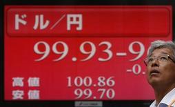 Мужчина проходит мимо экрана с курсом доллара США к японской иене в Токио 3 июля 2013 года. Иена растет после убедительной победы правящего блока премьер-министра Синдзо Абэ на выборах в верхнюю палату парламента, дающей Абэ возможность продолжать политику по борьбе с дефляцией. REUTERS/Issei Kato