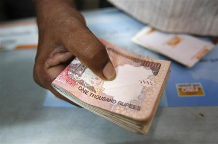 A customer hands a bundle of Indian Rupee currency notes to a teller at a financial institution in Mumbai July 2, 2013. REUTERS/Vivek Prakash