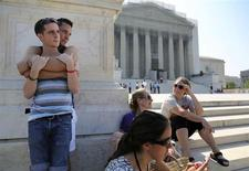 Chase Hardin (L) and Sam Knode (2nd L) join gay marriage supporters and court watchers hoping for U.S. Supreme Court rulings in the cases against California's gay marriage ban known as Prop 8 and the 1996 federal Defense of Marriage Act (DOMA), outside the court building in Washington, June 25, 2013. REUTERS/Jonathan Ernst