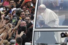 Pope Francis kisses a baby while greeting the crowd of faithful from his popemobile in downtown Rio de Janeiro, July 22, 2013. REUTERS/Ueslei Marcelino