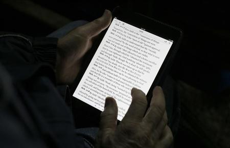 A man reads the bible from an iPad mini at the ''Christ is the Answer International Ministries'' group's camp near Florence February 2, 2013. REUTERS/Max Rossi