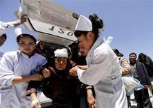 Медсестры помогают пострадавшей при землетрясении женщине в провинции Ганьсу 22 июля 2013 года. Количество погибших после двух землетрясений в китайской провинции Ганьсу возросло до 89 человек, более 500 человек получили серьезные ранения, сообщило новостное агентство Синьхуа. REUTERS/China Daily