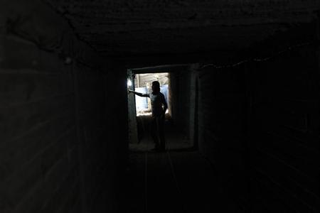 A Palestinian tunnel worker adjusts a lamp inside a smuggling tunnel dug beneath the Gaza-Egypt border in the southern Gaza Strip July 19, 2013. REUTERS/Ibraheem Abu Mustafa