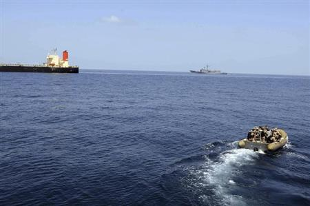 A rigid-hull inflatable boat from the guided-missile destroyer USS Bulkeley (DDG 84) approaches the Japanese-owned commercial oil tanker M/V Guanabara (L) in the Arabian Sea off the Coast of Somalia on March 6, 2011 in this picture released to Reuters March 7, 2011. REUTERS/Seaman Anna Wade/U.S. Navy photo/Handout