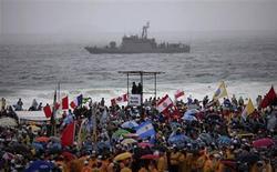 Pilgrims cheer, as policemen patrol on a deck and a Brazilian Navy ship patrols the coast ahead the World Youth Day in Rio de Janeiro July 23, 2013. REUTERS/Ricardo Moraes