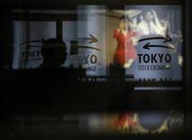 Мужчина проходит мимо окон с логотипами Токийской фондовой биржи в Токио 13 июня 2013 года. Азиатские фондовые рынки завершили торги среды разнонаправленно на фоне квартальной отчетности Apple и китайского PMI. REUTERS/Toru Hanai