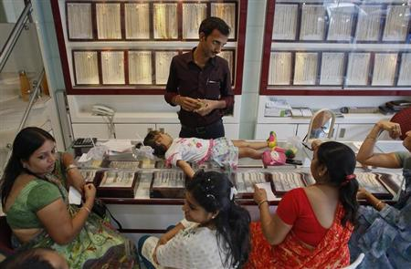 An employee counts money, as a child lies on the counter, following purchases of gold jewellery inside a showroom in Mumbai June 4, 2013. REUTERS/Danish Siddiqui/Files