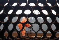 Рабочие разгружают партию стальных труб в порту вьетнамского города Хайфон 14 марта 2012 года. Американское министерство торговли во вторник начало одно из своих самых крупных торговых расследований за последние годы по обвинениям производителей Южной Кореи, Индии и семи других стран в поставках в США стальных труб для нефтегазовой промышленности по несправедливо низким ценам. REUTERS/Kham