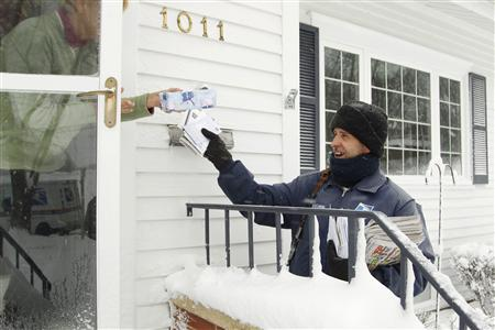 Mail carrier Mike Perkins delivers mail in the snow along Fletcher Avenue in Waterloo, Iowa, December 20, 2012. REUTERS/Matthew Putney/The Waterloo Courier/Handout