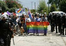 Riot police protect LGBT activists during a gay pride parade in Budva July 24, 2013. REUTERS/Stevo Vasiljevic
