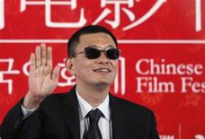 """Director Wong Kar-wai waves during a news conference to promote his movie """"The Grandmaster"""", the opening film of the Chinese Film Festival, in Seoul June 16, 2013. REUTERS/Kim Hong-Ji"""