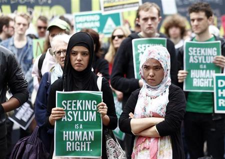 A woman holds a poster during a rally in support of asylum seekers in central Sydney July 20, 2013. REUTERS/Daniel Munoz