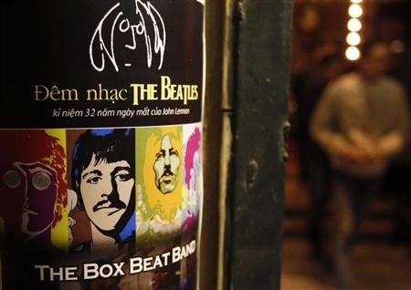 A fan walks near a poster promoting a tribute concert which marks the 32nd death anniversary of British legendary rocker John Lennon of the Beatles at a vintage cafe in Hanoi December 7, 2012. REUTERS/Kham/Files