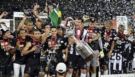 Capitão do Atlético Mineiro, Rever segura o troféu de campeão da Copa Libertadores da América, após vencer a segunda partida da final contra o time paraguaio Olimpia, no estádio do Mineirão, Belo Horizonte. O Atlético Mineiro conseguiu mais uma vez fazer o que parecia impossível na Copa Libertadores e, diante de uma torcida apaixonada, conquistou seu primeiro título da Copa Libertadores, na quarta-feira, com uma vitória por 4 x 3 na disputa de pênaltis sobre o Olimpia, após reverter uma derrota por 2 x 0 sofrida no primeiro jogo da decisão. 24/07/2013. REUTERS/Pedro Vilela