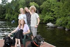 """Writer Jennifer Finney Boylan, author of the book """"Stuck in the Middle with You,"""" sits with her spouse Deidre and their sons Zach and Sean (L-R) outside their lake house in Maine in 2012, in this photo courtesy of the Boylan family. REUTERS/Boylan family/Handout via Reuters"""