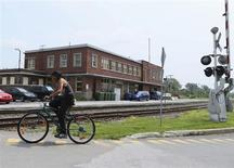 A cyclist rides past the building of the Maine, Montreal and Atlantic Railways (MMA), whose oil-tanker exploded last Saturday, in the town of Farnham, Quebec July 10, 2013. REUTERS/Christinne Muschi