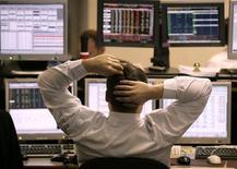 Трейдер инвесткомпании Троки Диалог на рабочем месте в Москве 20 декабря 2004 года. Российские фондовые индексы в пятницу колеблются без заметных изменений после снижения предыдущих сессий, а бумаги Магнита и отскочившие после падения акции Уралкалия прибавили чуть более одного процента. REUTERS/Alexander Natruskin