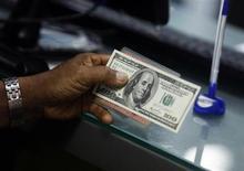 Мужчина держит свое удостоверение личности и банкноту в 100 долларо США в пункте обмена валют в Янгоне 2 апреля 2012 года. Доллар снизился до минимума пяти недель к корзине мировых валют перед совещанием ФРС на будущей неделе. REUTERS/Soe Zeya Tun