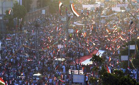 Anti-Mursi protesters shout slogans as they wave Egyptian national flags during a rally and march around El-Thadiya presidential palace in Cairo July 26, 2013. REUTERS-Amr Abdallah Dalsh