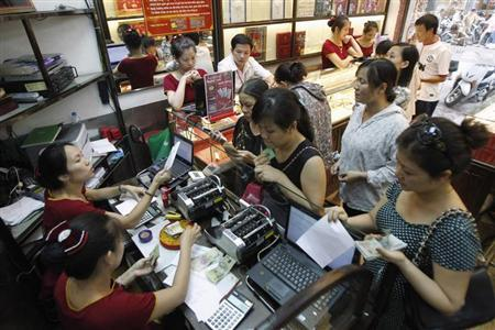Employees (L) count money as customers queue to buy gold at a Bao Tin Minh Chau gold shop in Hanoi June 21, 2013. REUTERS/Kham