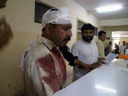 A man, who was injured in a blast, stands at a hospital in Parachinar July 26,2013. REUTERS/Stringer