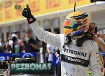 Piloto da equipe Mercedes Lewis Hamilton comemora a conquista da pole position nos treinos oficiais para o Grande Prêmio da Hungria de Fórmula 1, no circuito Hungaroring, Mogyorod, próximo a Budapeste. Hamilton conquistou sua terceira pole position consecutiva com a Mercedes sob intenso calor na pista da Hungria neste sábado. 27/07/2013. REUTERS/Bernadett Szabo