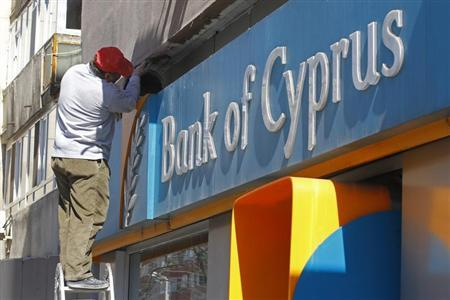A worker paints a wall above a branch of Bank of Cyprus in Bucharest April 1, 2013. Cyprus' biggest bank suspended its Romanian operations for one week from Monday as part of a reorganisation under a rescue deal with the European Union to stave off national bankruptcy. REUTERS/Bogdan Cristel