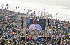 Pilgrims watch Pope Francis on a video screen as he celebrates mass on Copacabana Beach in Rio de Janeiro, July 28, 2013. REUTERS/Maria Luiz Mesquita-O Dia