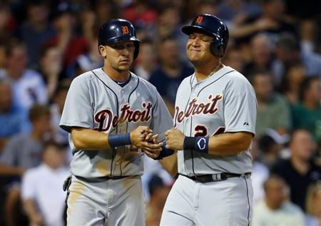 Detroit Tigers third baseman Miguel Cabrera (R) grimaces as he celebrates after scoring in the top of the fifth inning with teammate Hernan Perez (L) against the Chicago White Sox during their MLB baseball game in Chicago, July 22, 2013. REUTERS/Jeff Haynes