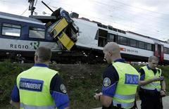 Сотрудники полиции и спасатели у места столкновения поездов в Гранж-пре-Марнан, Швейцария 29 июля 2013 года. По меньшей мере 35 из 40 пассажиров пострадали, пять из них тяжело, в столкновении двух поездов в Швейцарии вечером в понедельник, сообщила полиция. REUTERS/Denis Balibouse