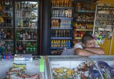Уличный торговец в ожидании покупателей в Крыму 14 июня 2013 года. Международный валютный фонд планирует в рамках программы пост-мониторинга провести тщательную проверку экономической политики Украины, еще не погасившей значительную сумму ранее взятых кредитов фонда. REUTERS/Gleb Garanich