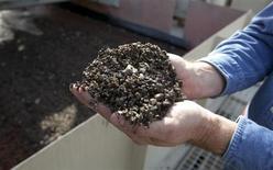 Работник Mosaic Co держит фосфатную руду на шахте в Форт-Миде, Флорида, 13 января 2010 года. Российский агрохимический холдинг Фосагро, второй по величине производитель фосфорных удобрений в мире, увеличил выпуск удобрений на 12,9 процента в первом полугодии 2013 года. REUTERS/Scott Audette