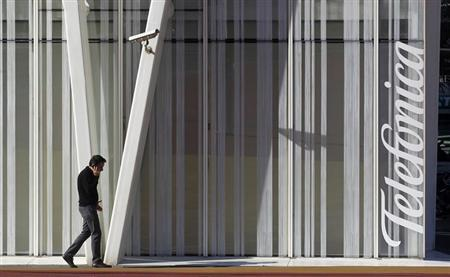 A man speaks by a mobile next to Telefonica's tower in Barcelona January 30, 2013. REUTERS/Albert Gea/Files