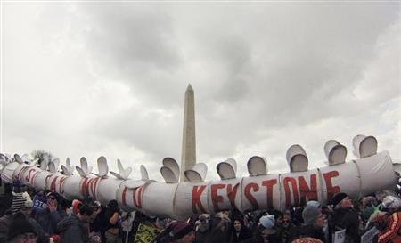 Demonstrators carry a replica of a pipeline during a march against the Keystone XL pipeline in Washington, February 17, 2013. REUTERS/Richard Clement