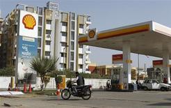 Мотоциклист проезжает мимо АЗС Shell в Ахмедабаде 6 февраля 2013 года. Нефтегазовая компания Royal Dutch Shell снизила прибыль во втором квартале в связи с ростом расходов, воровством нефти и перебоями в добыче в Нигерии. REUTERS/Amit Dave